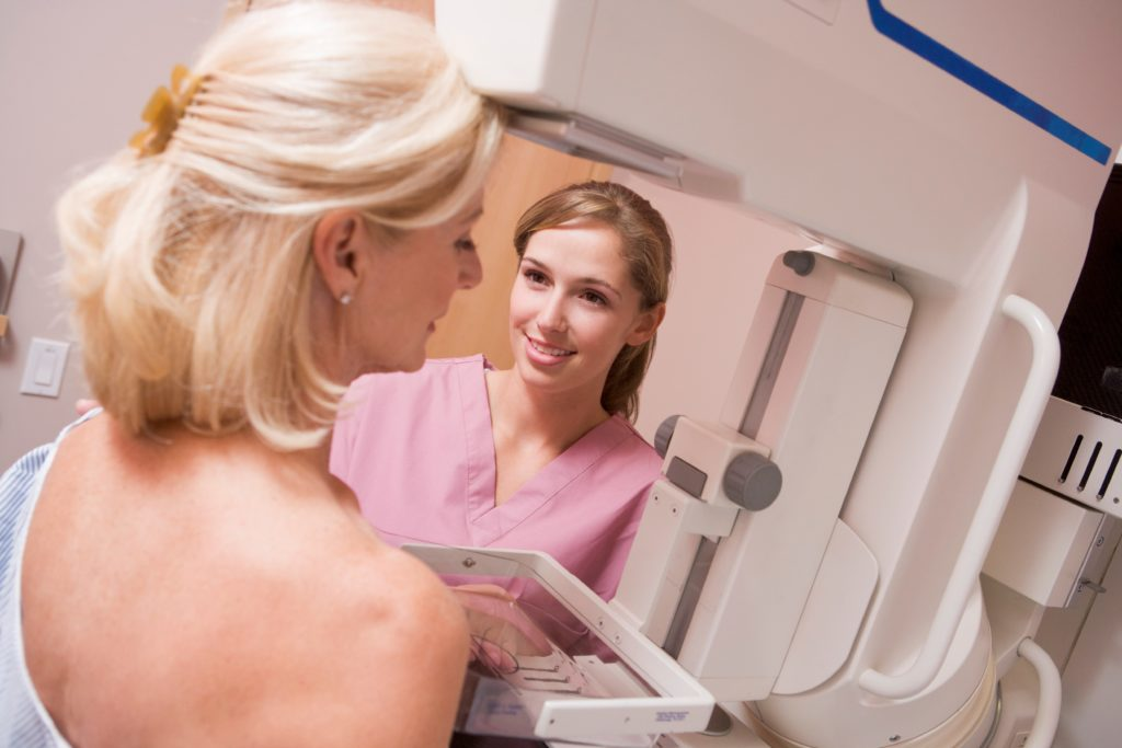 Woman receives mammogram from female nurse.